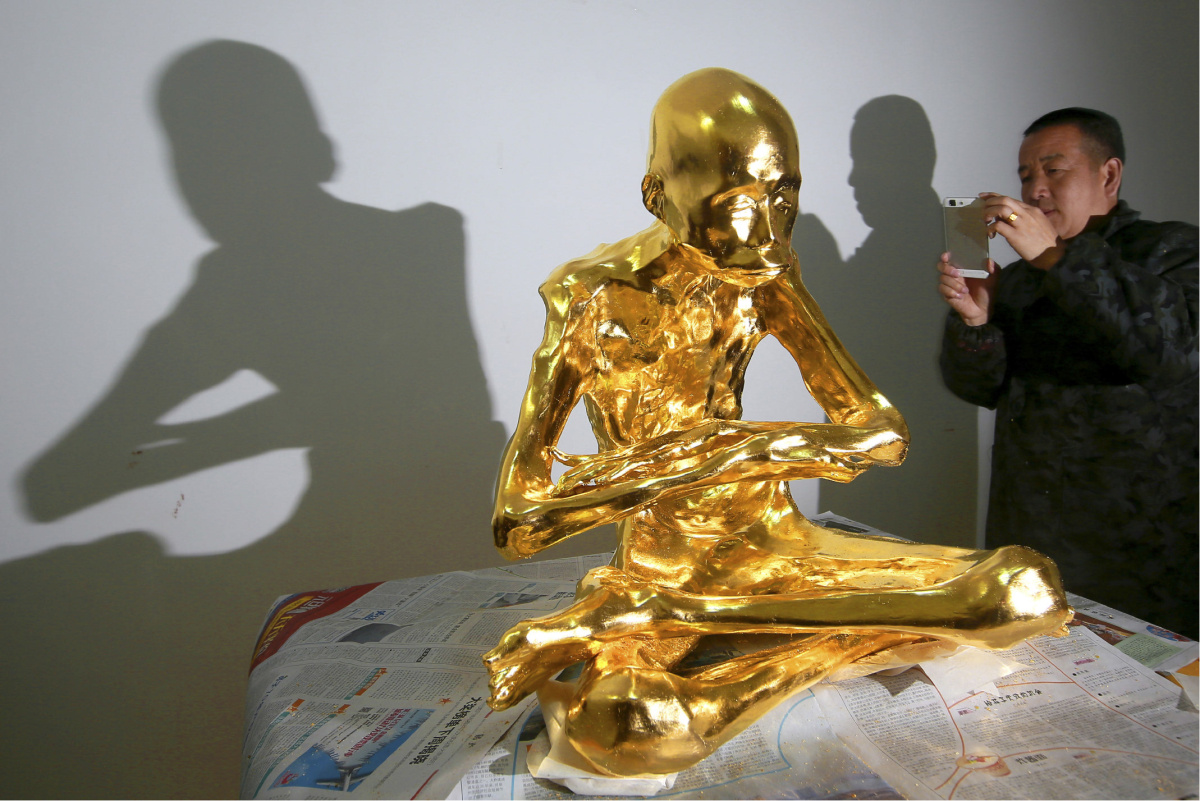 In this photo taken March 16, 2016, a man takes a photo of the mummified body of revered Buddhist monk Fu Hou in Quanzhou city in southeastern China's Fujian province. The monk, who died in 2012 at the age of 94, was prepared for mummification by his temple to commemorate his devotion to Buddhism. The mummifed remains were then treated and covered in gold leaf, a practice reserved for holy men in some areas with strong Buddhist traditions. (Chinatopix via AP) CHINA OUT